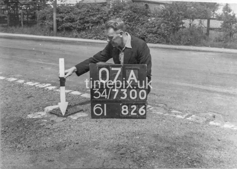 SD730007A, Man marking Ordnance Survey minor control revision point with an arrow in 1940s