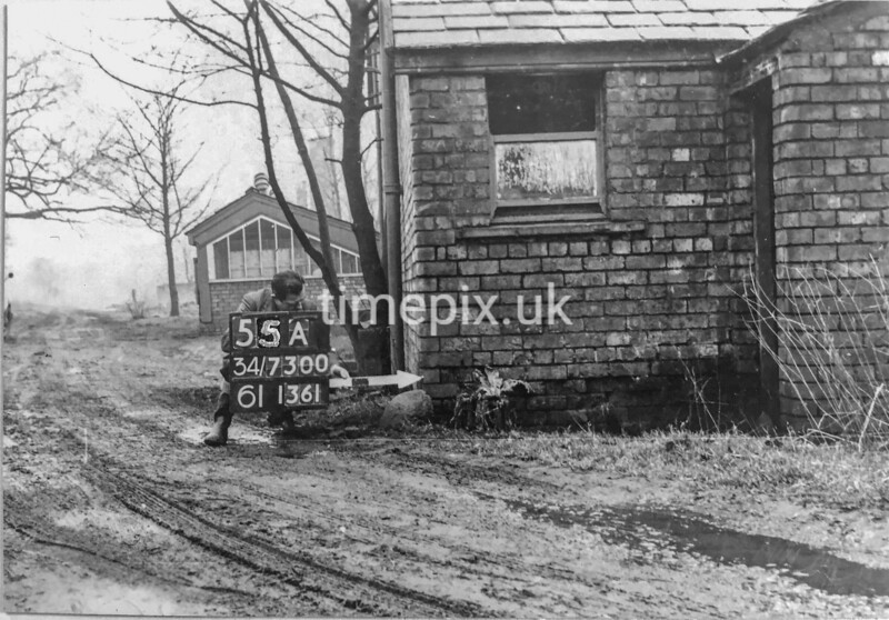 SD730055A, Man marking Ordnance Survey minor control revision point with an arrow in 1950s