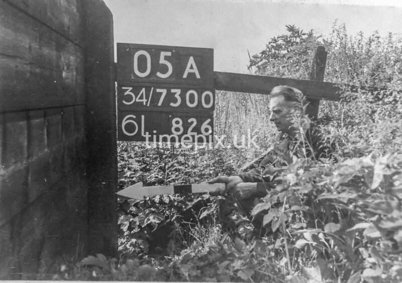 SD730005A, Man marking Ordnance Survey minor control revision point with an arrow in 1940s