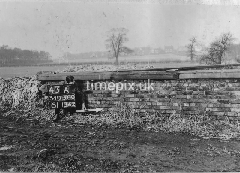SD730043A, Man marking Ordnance Survey minor control revision point with an arrow in 1950s
