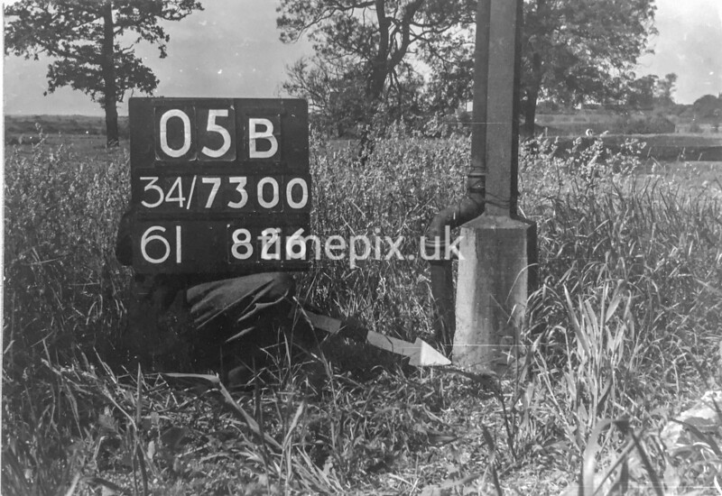 SD730005B, Man marking Ordnance Survey minor control revision point with an arrow in 1940s