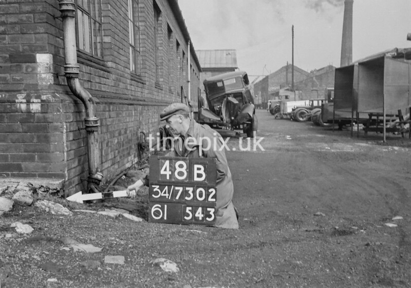 SD730248B, Man marking Ordnance Survey minor control revision point with an arrow in 1940s