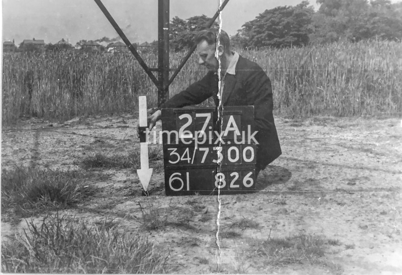 SD730027A, Man marking Ordnance Survey minor control revision point with an arrow in 1940s