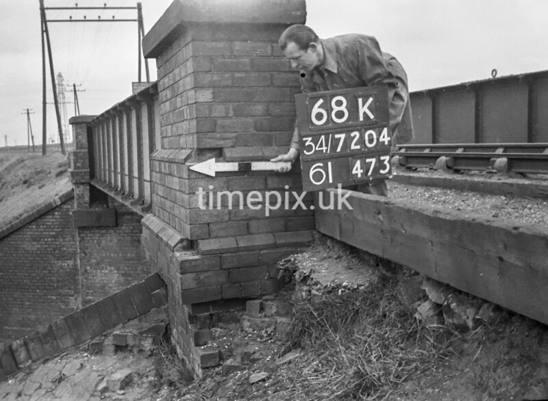 SD720468K, Man marking Ordnance Survey minor control revision point with an arrow in 1950s