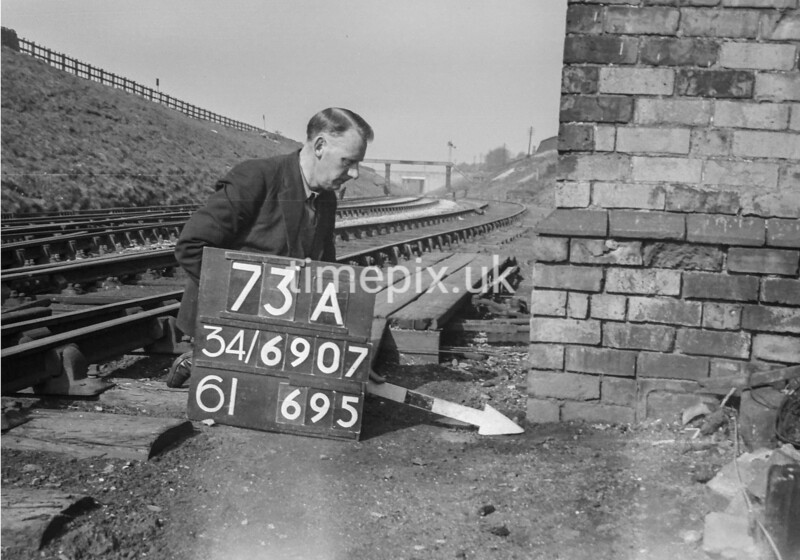 SD690773A, Man marking Ordnance Survey minor control revision point with an arrow in 1950s