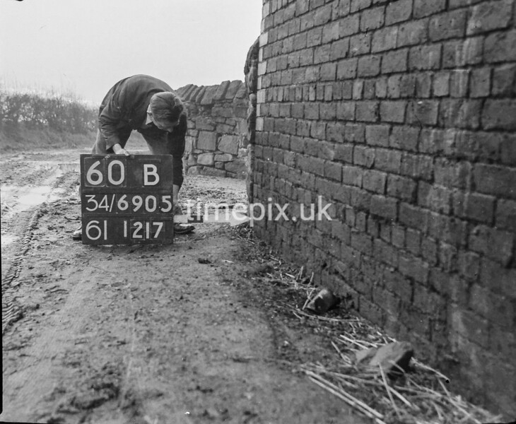 SD690560B2, Man marking Ordnance Survey minor control revision point with an arrow in 1950s