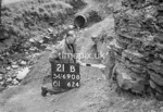 SD690821B, Man marking Ordnance Survey minor control revision point with an arrow in 1950s