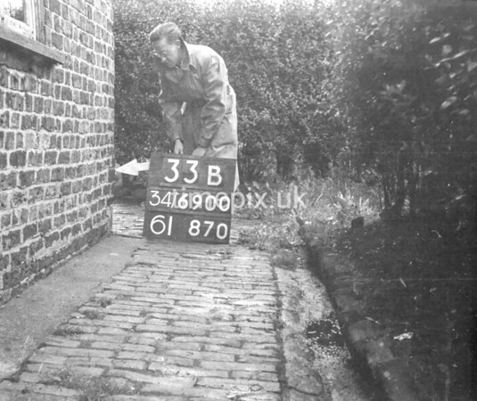 SD690033B, Man marking Ordnance Survey minor control revision point with an arrow in 1950s
