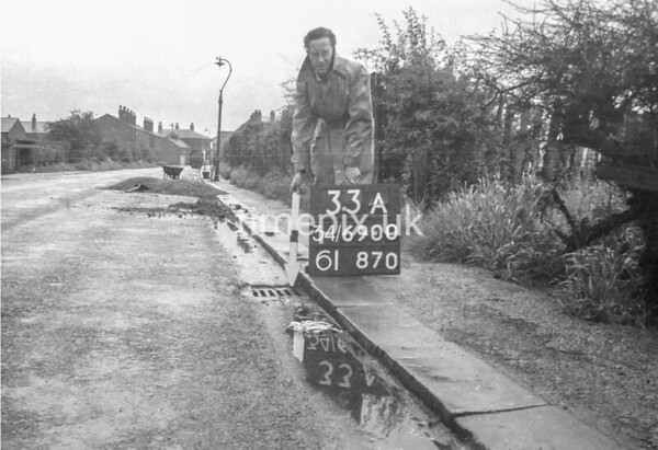SD690033A, Man marking Ordnance Survey minor control revision point with an arrow in 1950s