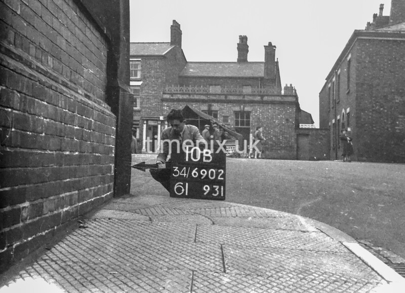 SD690210B2, Man marking Ordnance Survey minor control revision point with an arrow in 1950s