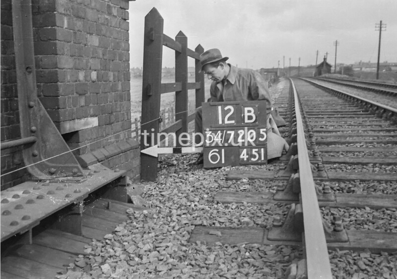 SD720512B, Man marking Ordnance Survey minor control revision point with an arrow in 1950s