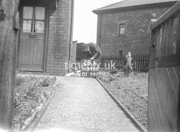 SD690028A, Man marking Ordnance Survey minor control revision point with an arrow in 1950s