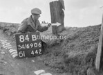 SD690684B, Man marking Ordnance Survey minor control revision point with an arrow in 1950s