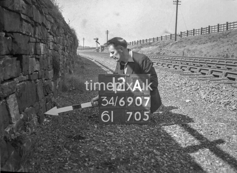 SD690712A, Man marking Ordnance Survey minor control revision point with an arrow in 1950s