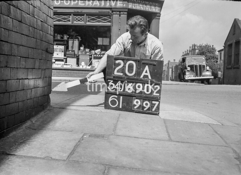 SD690220A, Man marking Ordnance Survey minor control revision point with an arrow in 1950s