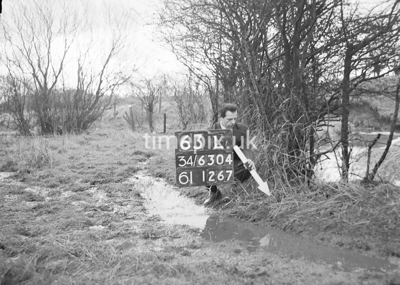 SD630463L, Man marking Ordnance Survey minor control revision point with an arrow in 1940s