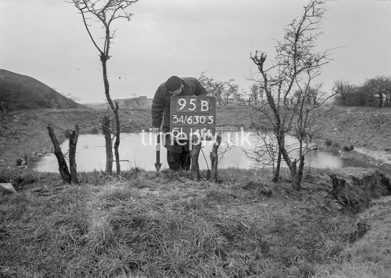 SD630595B, Man marking Ordnance Survey minor control revision point with an arrow in 1940s