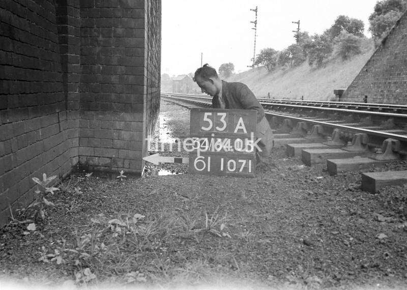 SD640553A, Man marking Ordnance Survey minor control revision point with an arrow in 1940s