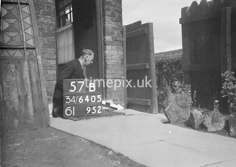 SD640557B, Man marking Ordnance Survey minor control revision point with an arrow in 1940s