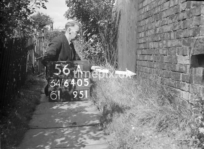 SD640556A, Man marking Ordnance Survey minor control revision point with an arrow in 1940s