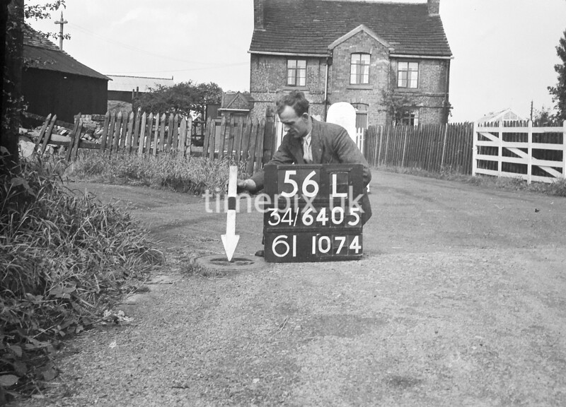 SD640556L, Man marking Ordnance Survey minor control revision point with an arrow in 1940s