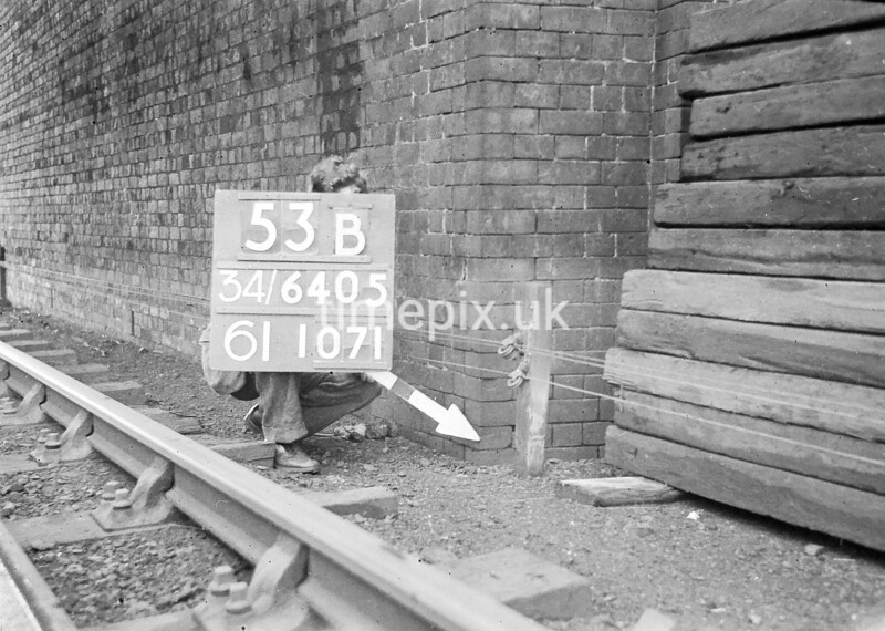 SD640553B, Man marking Ordnance Survey minor control revision point with an arrow in 1940s