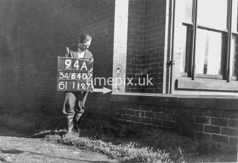 SD640794A, Man marking Ordnance Survey minor control revision point with an arrow in 1940s