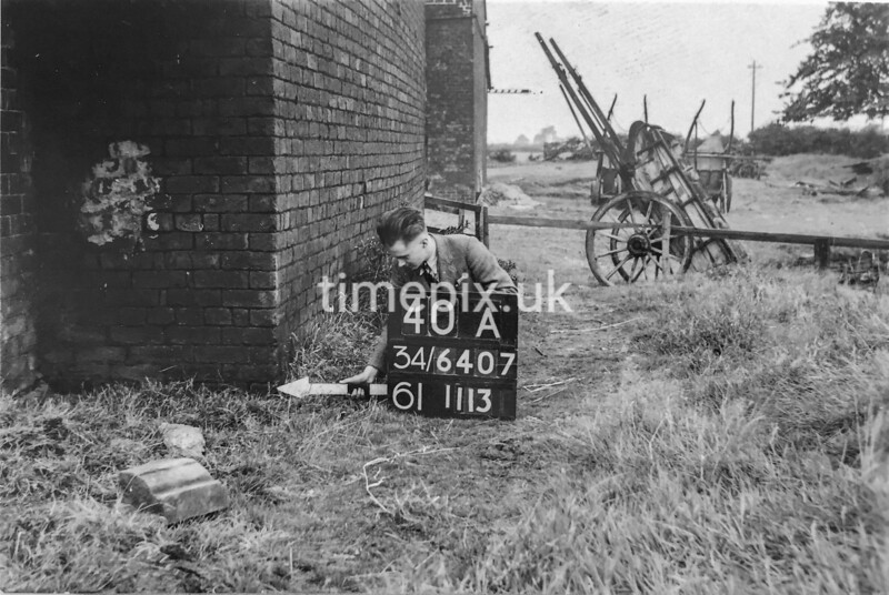 SD640740A, Man marking Ordnance Survey minor control revision point with an arrow in 1940s