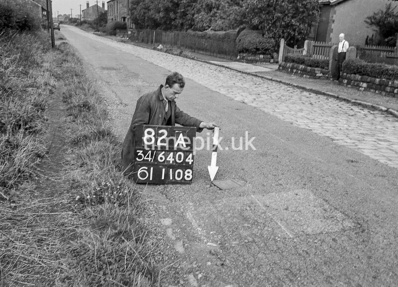 SD640482A, Man marking Ordnance Survey minor control revision point with an arrow in 1940s