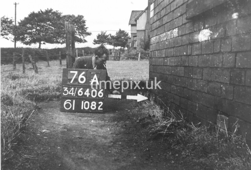 SD640676A, Man marking Ordnance Survey minor control revision point with an arrow in 1940s