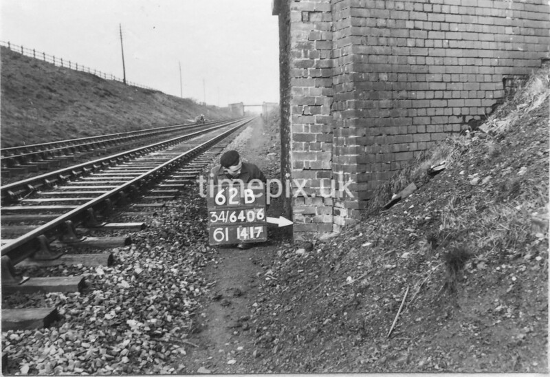 SD640662B, Man marking Ordnance Survey minor control revision point with an arrow in 1950s