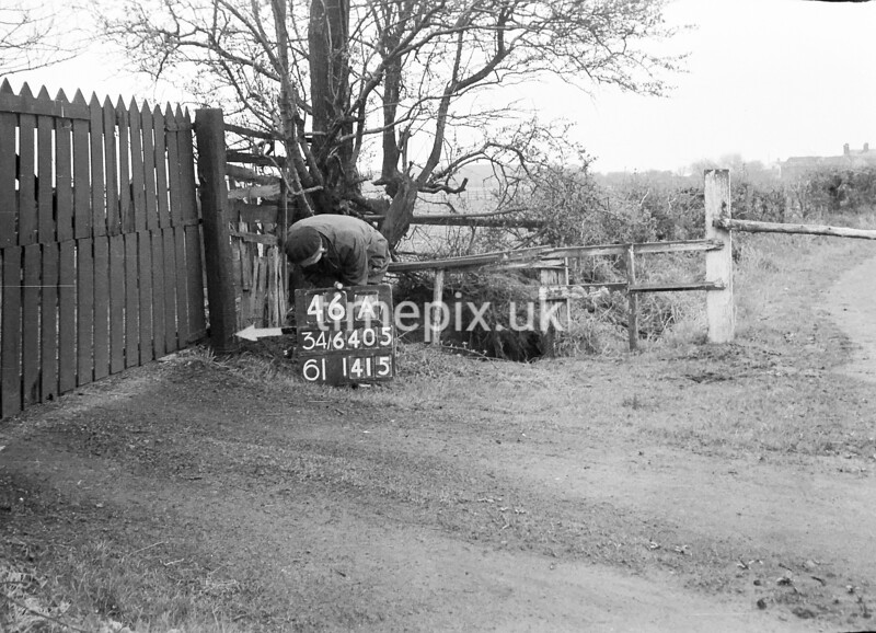 SD640546A, Man marking Ordnance Survey minor control revision point with an arrow in 1940s