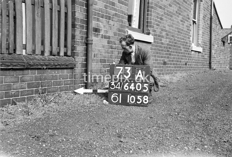 SD640573A, Man marking Ordnance Survey minor control revision point with an arrow in 1940s