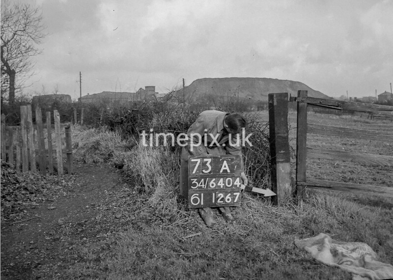 SD640473A, Man marking Ordnance Survey minor control revision point with an arrow in 1940s