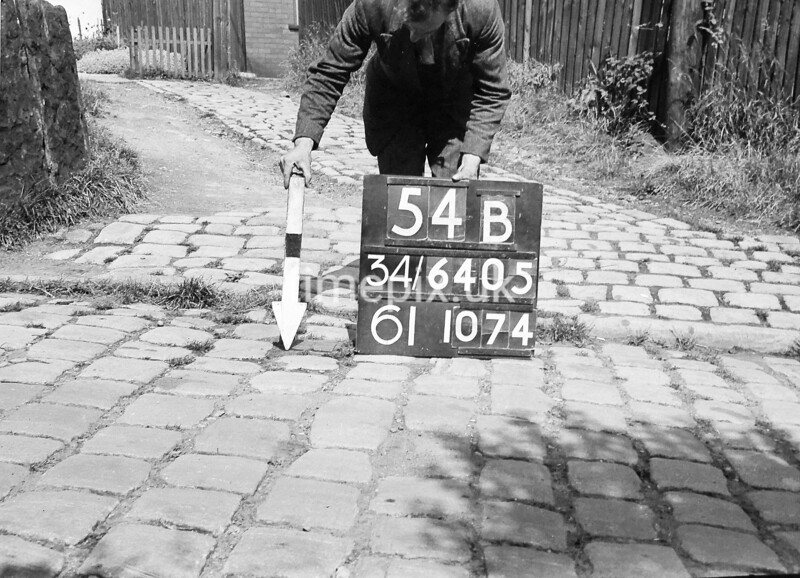 SD640554B, Man marking Ordnance Survey minor control revision point with an arrow in 1940s