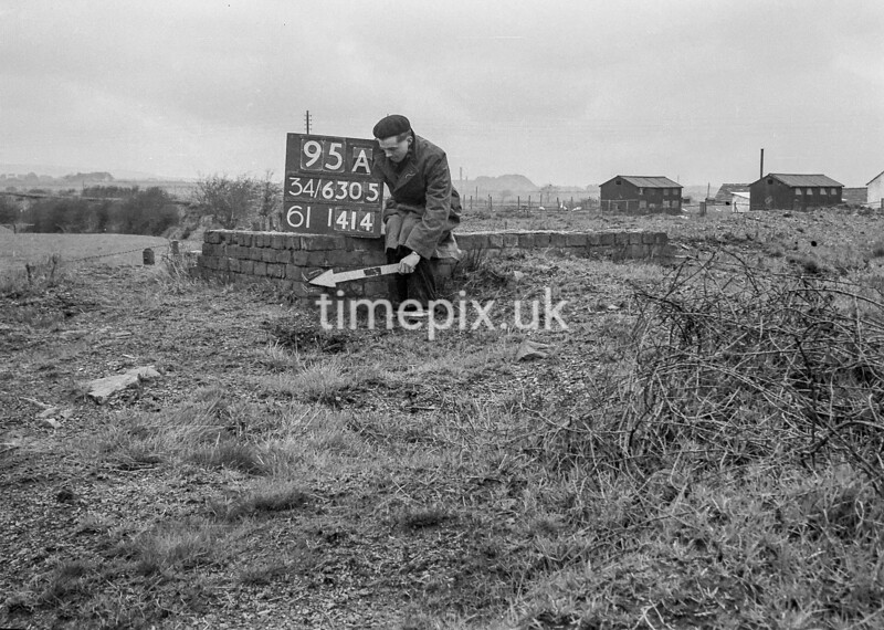 SD630595A, Man marking Ordnance Survey minor control revision point with an arrow in 1940s