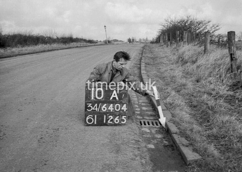 SD640410A, Man marking Ordnance Survey minor control revision point with an arrow in 1940s