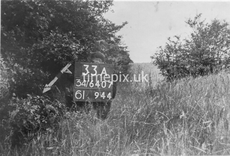 SD640733A, Man marking Ordnance Survey minor control revision point with an arrow in 1940s