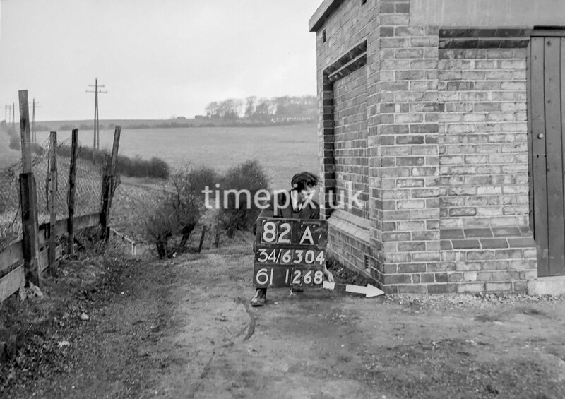 SD630482A, Man marking Ordnance Survey minor control revision point with an arrow in 1940s