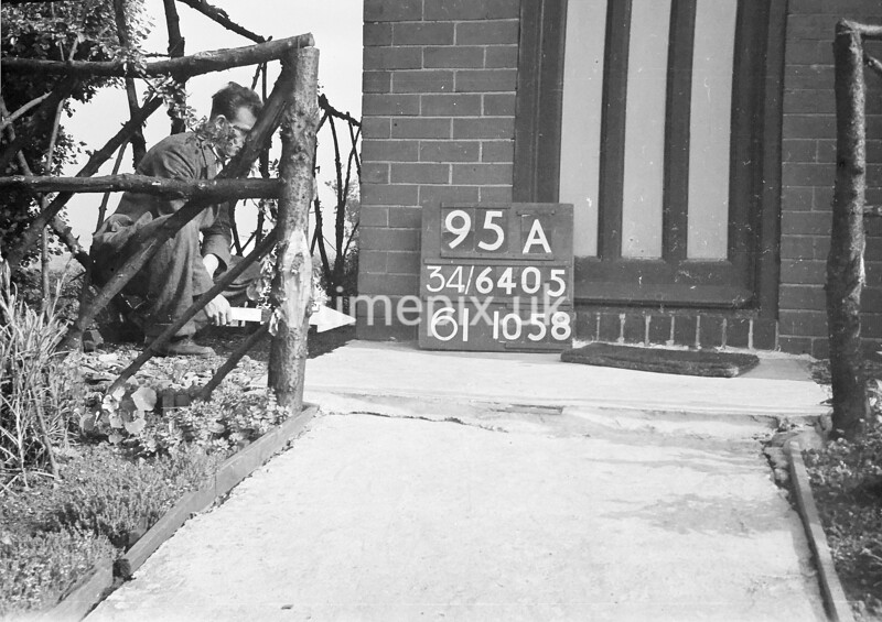 SD640595A, Man marking Ordnance Survey minor control revision point with an arrow in 1940s