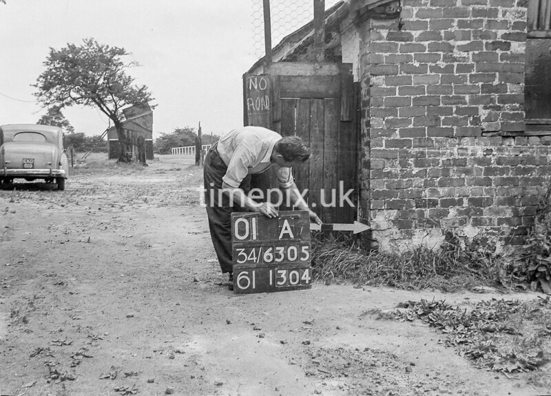 SD630501A, Man marking Ordnance Survey minor control revision point with an arrow in 1940s
