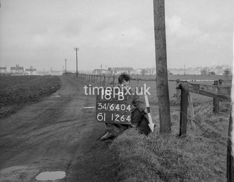 SD640418B, Man marking Ordnance Survey minor control revision point with an arrow in 1940s