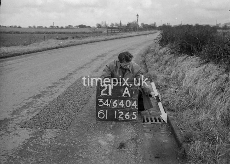 SD640421A, Man marking Ordnance Survey minor control revision point with an arrow in 1940s