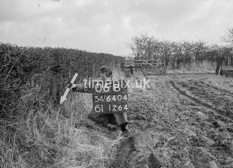SD640406B, Man marking Ordnance Survey minor control revision point with an arrow in 1940s