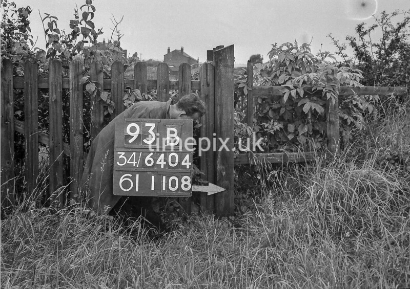 SD640493B, Man marking Ordnance Survey minor control revision point with an arrow in 1940s