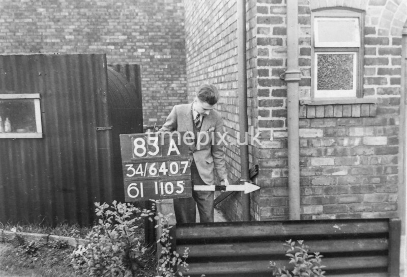 SD640783A, Man marking Ordnance Survey minor control revision point with an arrow in 1940s