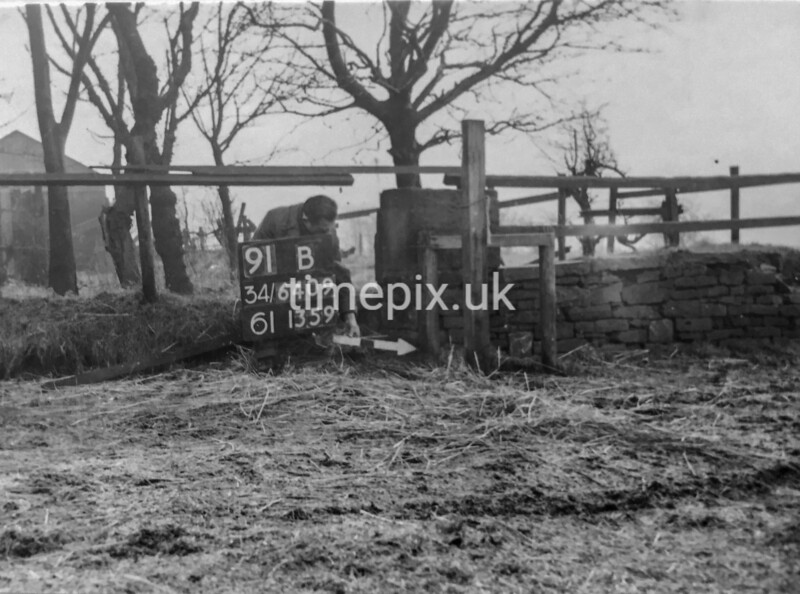 SD640991B, Man marking Ordnance Survey minor control revision point with an arrow in 1940s