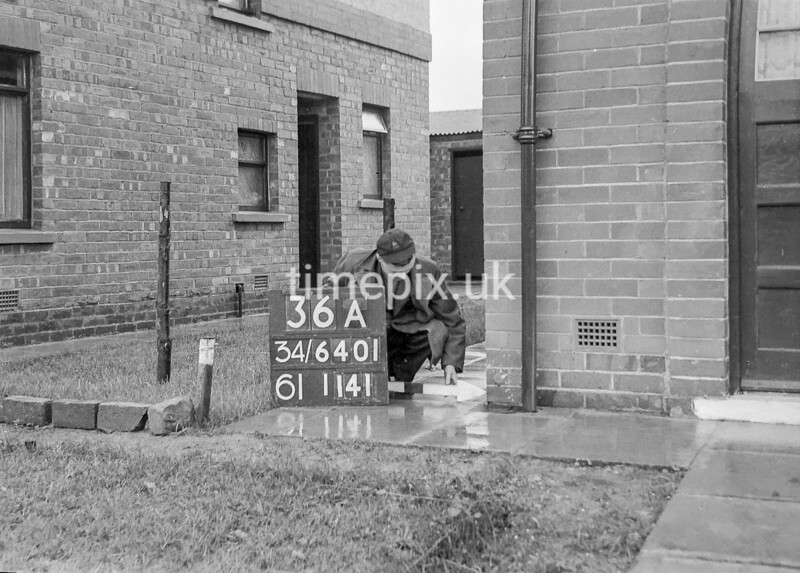SD640136A, Man marking Ordnance Survey minor control revision point with an arrow in 1940s