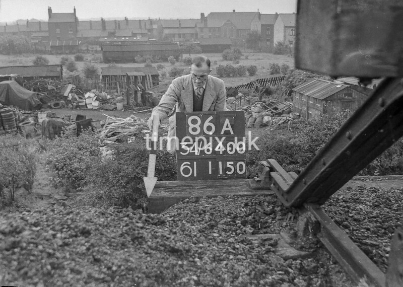 SD640086A, Man marking Ordnance Survey minor control revision point with an arrow in 1940s