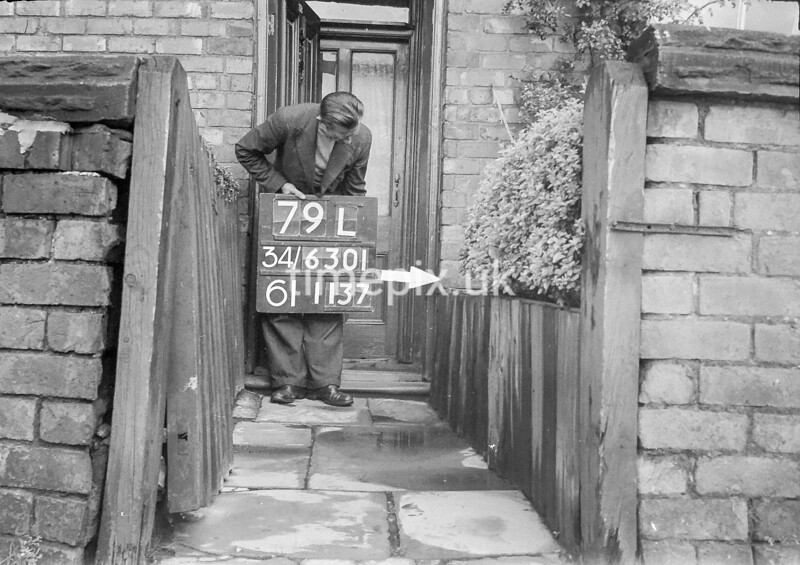 SD630179L, Man marking Ordnance Survey minor control revision point with an arrow in 1940s